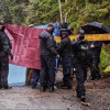 RCMP officers hold a tarp to block the view of an arrest from reporters and the public while one officer directs a photographer to move back to a position where they cannot see beyond the tarp.
